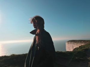 Lady standing outdoors, on a grassy cliff edge with the sky and water meeting at the horizon in the background