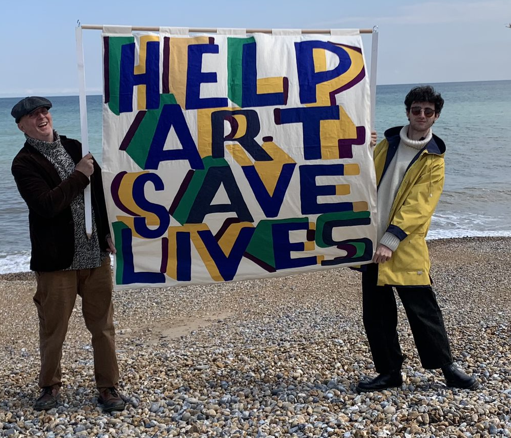 Two people standing on a pebbly sea shore holding up a sign reading: Help Art Save Lives