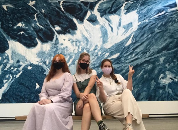 Students sat on a bench with an Exhibition with artwork behind them