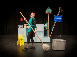 A lady on a theatre set with various cleaning equipment surrounding her. She told a mop in a very enthusiastic manner smiling.