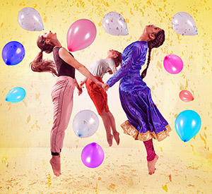 3 people holding hands leaping upwards surrounded by coloured balloons also in the air