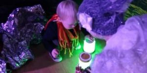 A toddler playing with a light with the aid of an adult in theatrical costume