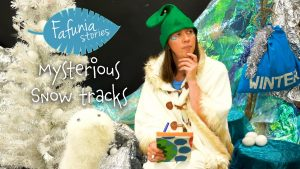 A poster of a woman dressed in costume looking pensively with her hand on her chin looking into the distance. she sits amidst and winter-like setting created with a character sitting beside her, a christmas tree amd a bag with 'winter' written on it and tinsel coming out