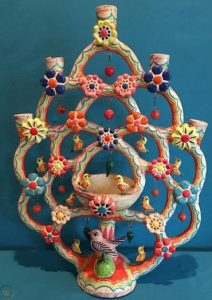 A colourful tree of life sculpture with detailing including birds, flowers and patterns.