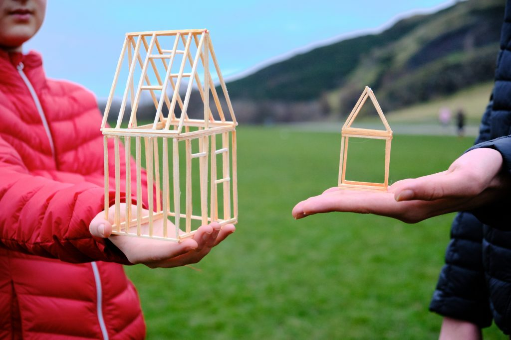 two people, a boy and man, hold models of houses on their palms