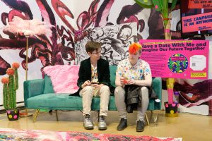 two people sit on a green sofa, in frontt of pink tentacles on the wall