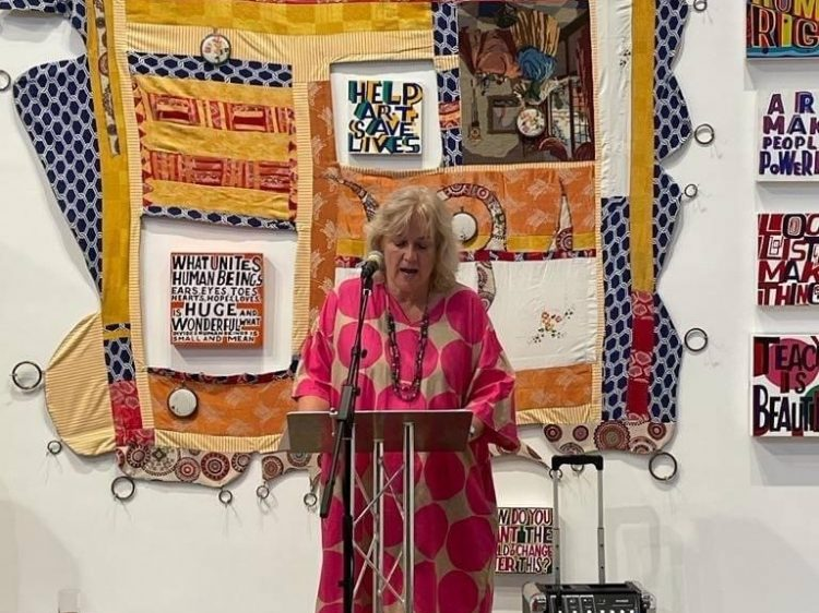 Michaela talking at a podium, in front of a large, textile art piece