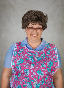 Person smiling at the camera wearing glasses, a blue shirt with a pink floral apron