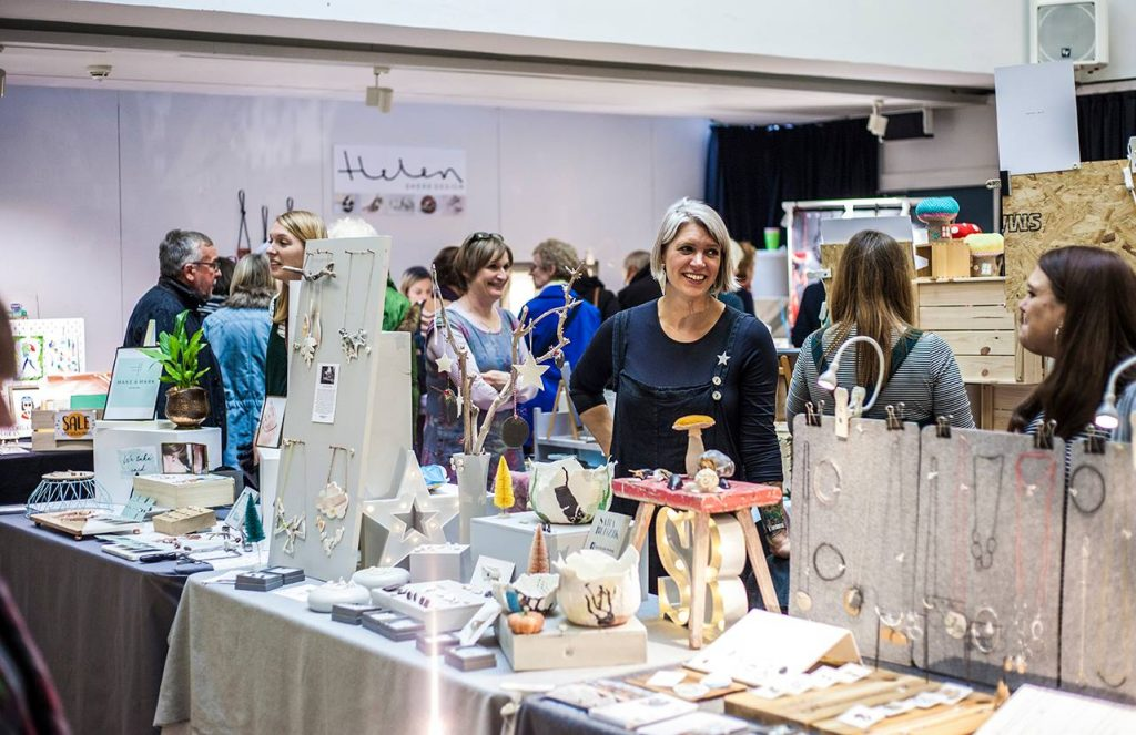 Stall holders displaying various merchandise such as jewellery, arts and crafts at a craft fair