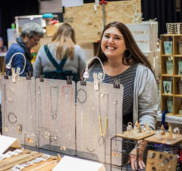 Stall holder smiling displaying various merchandise such as jewellery at a craft fair