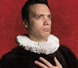 A man dressed in Tudor fashion in front of a red background, looking diagonally up with a questioning look on his face