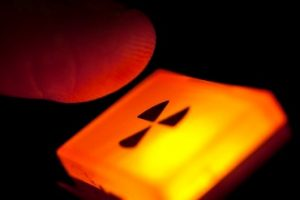 Finger is shown above a nuclear radiation button that is lit up orange