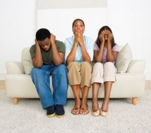 A man and two women sitting on the sofa, making 'see no evil, hear no evil, speak no evil' gestures