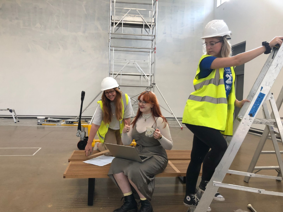 two women in high vis, one on a stepladder, and a third sat with a laptop